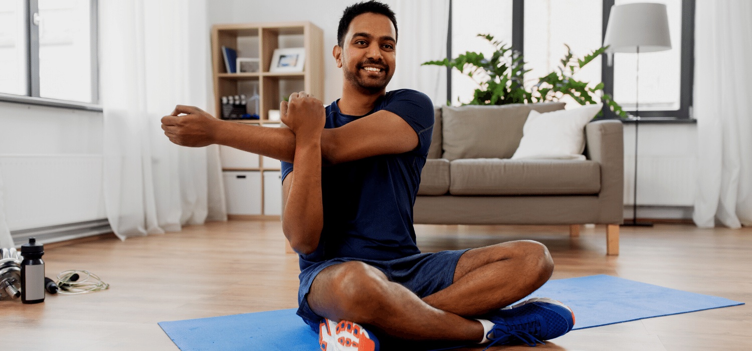 Husband Practicing Self Care By Stretching During COVID19 as Suggested in Relationship Therapy